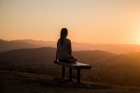 Woman on bench at sunset