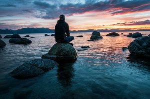 Man on stone by water sunset